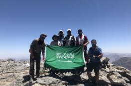 رحالة سعودي يرفع علم المملكة على قمة جبل شمس